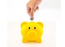 Entregue a colocação de uma moeda no mealheiro plástico amarelo no branco para trás Fotos de Stock Royalty Free