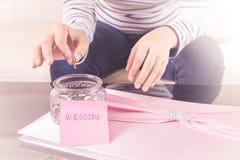 Entregue a colocação de uma moeda nos frascos de vidro com texto 'do casamento' foto de stock