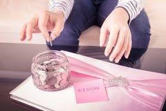 Entregue a colocação de uma moeda nos frascos de vidro com texto 'do casamento' foto de stock royalty free