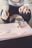 Entregue a colocação de uma moeda nos frascos de vidro com texto 'do casamento' fotos de stock royalty free