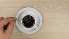 Entregue a colocação do açúcar da colher em uma xícara de café e em um stirring ele para estabelecer a colher nos pires vídeos de arquivo