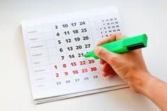 Entregue cruzes fora dos dias verdes do marcador no calendário Calendário branco Os fins de semana são destacados no vermelho Fim imagens de stock