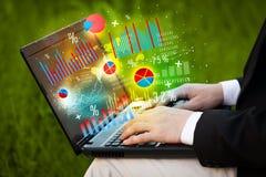 Entregue a datilografia no laptop moderno do portátil com ícones do gráfico Imagens de Stock