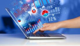 Entregue a datilografia no laptop moderno do portátil com ícones do gráfico Fotografia de Stock Royalty Free