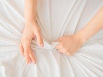 Entregue embreagens ou apertos uma folha de cama amarrotada branco em uma sala de hotel, um sinal da êxtase, sentimento do prazer imagem de stock royalty free