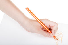 Entregue esboços pelo lápis alaranjado na folha de papel Imagem de Stock