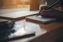 Entregue a escrita em um caderno vazio com portátil e tabuleta no fundo de madeira da tabela Fotografia de Stock Royalty Free