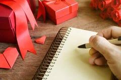 Entregue a escrita no caderno com caixa de presente e a flor vermelhas em de madeira Imagem de Stock