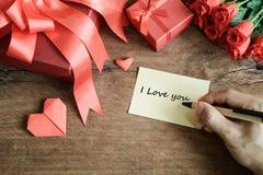 Entregue a escrita no caderno com caixa de presente e a flor vermelhas em de madeira Fotografia de Stock