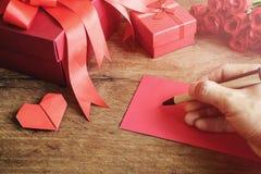Entregue a escrita no caderno com caixa de presente e a flor vermelhas em de madeira Imagens de Stock