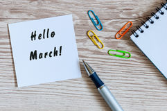 Entregue a escrita olá! março no pedaço de papel perto dos suplies do escritório na tabela de madeira Começo do conceito da mola Fotografia de Stock Royalty Free