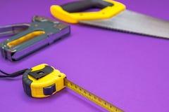 Entregue a ferramentas o ruller amarelo, grampeador, fita métrica da serra da mão foto de stock royalty free