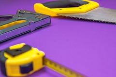 Entregue a ferramentas o ruller amarelo, grampeador, fita métrica da serra da mão imagem de stock