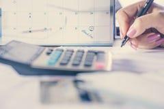 Entregue foco calculador do conceito do débito e do pagamento na nota do calendário do fim do prazo fotos de stock