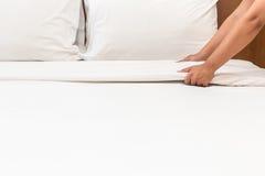 Entregue a folha de cama branca estabelecida na sala de hotel Imagens de Stock