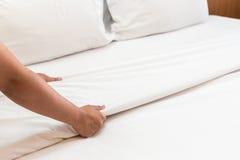 Entregue a folha de cama branca estabelecida na sala de hotel Foto de Stock Royalty Free