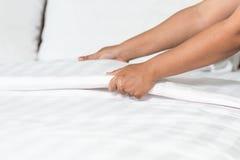 Entregue a folha de cama branca estabelecida na sala de hotel Fotos de Stock