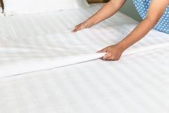 Entregue a folha de cama branca estabelecida na sala de hotel Imagem de Stock