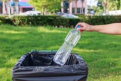 Entregue a garrafa plástica vazia de jogo no lixo Imagens de Stock Royalty Free