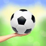 Entregue guardar a bola de futebol sobre o fundo brilhante da natureza Foto de Stock Royalty Free