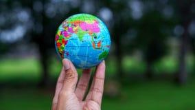 Entregue guardar a bola do globo do mundo com fundo do borrão imagem de stock royalty free