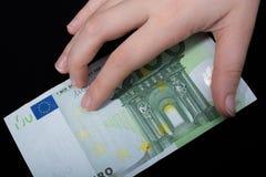 Entregue guardar a cédula do euro 100 em um fundo preto Fotos de Stock
