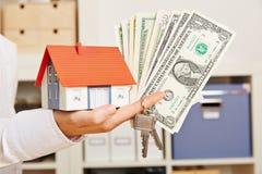 Entregue guardar a casa com chaves e dinheiro do dólar Imagens de Stock Royalty Free