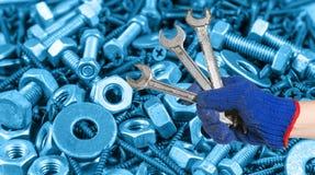 Entregue guardar a chave na porca e nos parafusos usados para o indu do equipamento Imagens de Stock