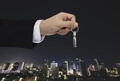 Entregue guardar chaves com fundo da cidade, bens imobiliários e conceito da propriedade imagem de stock royalty free