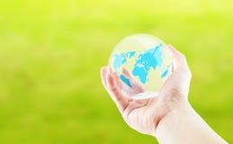 Entregue guardar em volta da bola lustrosa com o mapa do mundo no backgroun verde fotos de stock