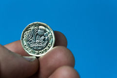Entregue guardar a moeda de libra BRITÂNICA nova em um fundo azul Imagens de Stock