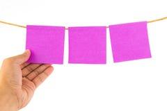 Entregue guardar a nota cor-de-rosa do papel vazio no fundo branco Imagem de Stock