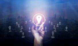 Entregue guardar o ícone do mapa do pino do lugar e a conexão de rede na cidade da tela imagens de stock royalty free