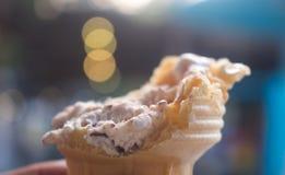 Entregue guardar o cone de gelado dos pedaços de chocolate no fundo do bokeh fotos de stock