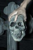 Entregue guardar o crânio no cemitério, efeito do filtro Fotografia de Stock Royalty Free
