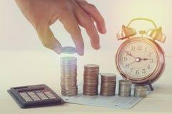 Entregue guardar o dinheiro na pilha das moedas e do conceito do despertador nas economias Fotografia de Stock