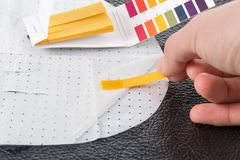 Entregue guardar o indicador de pH que compara a cor à escala imagens de stock