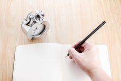 Entregue guardar o lápis preto e a escrita na sagacidade aberta do caderno da placa fotografia de stock