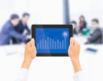 Entregue guardar o PC da tabuleta com gráfico financeiro mais alto no negócio Fotos de Stock Royalty Free