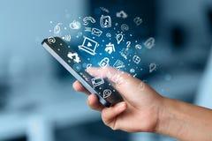 Entregue guardar o smartphone com ícones e símbolo dos meios Foto de Stock Royalty Free