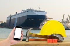 Entregue guardar o smartphone preto com o capacete de segurança amarelo em f Imagem de Stock Royalty Free