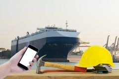Entregue guardar o smartphone preto com o capacete de segurança amarelo em f Fotografia de Stock Royalty Free