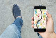 Entregue guardar o telefone esperto com aplicação da navegação dos gps do mapa Imagens de Stock Royalty Free