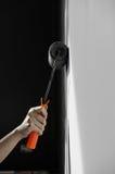 Entregue guardar a pintura do rolo que aplica a pintura cinzenta na parede branca Fotos de Stock Royalty Free