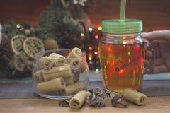 Entregue guardar um copo claro de vidro do chá com um tampão, uma bacia de cookies, uma grinalda do Natal Fotos de Stock Royalty Free