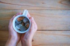 Entregue guardar um copo de moedas do baht tailandês na tabela de madeira Foto de Stock Royalty Free