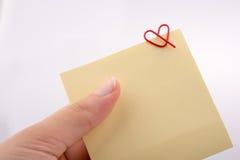 Entregue guardar um papel de nota com o grampo dado forma coração Fotografia de Stock