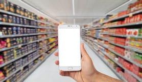 Entregue guardar um smartphone com a tela vazia no fundo do mercado super do borrão, copie o espaço fotografia de stock royalty free