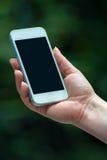 Entregue guardar um telefone contra o fundo verde do bokeh Fotografia de Stock