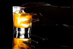 Entregue guardar um vidro do uísque nas rochas contra o fundo escuro Fotografia de Stock Royalty Free